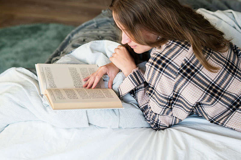 Woman laying in bed, reading a book